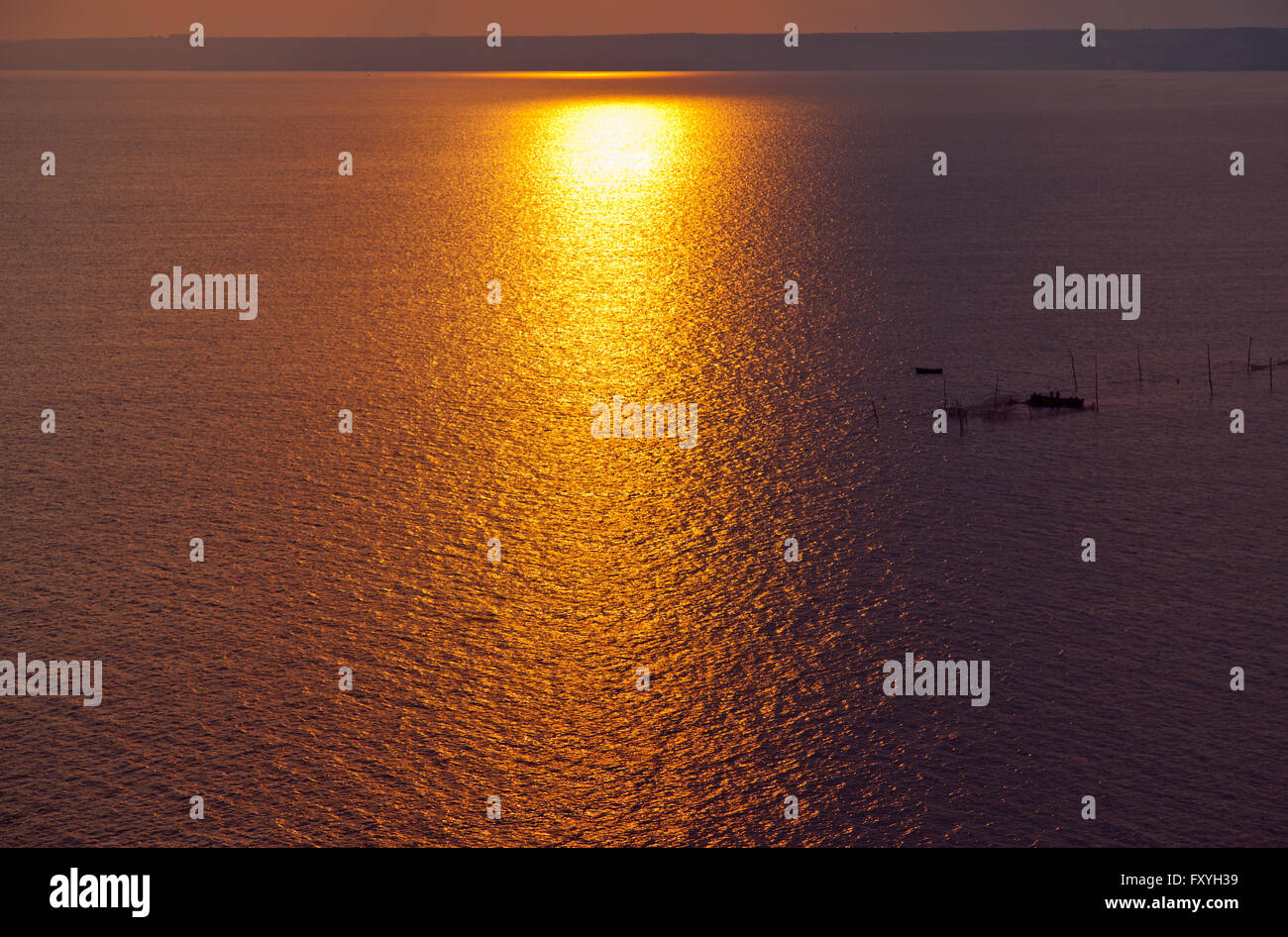 yewoll sunset or sunrise over a wide body of water - ocean , sea or lake. - Stock Image