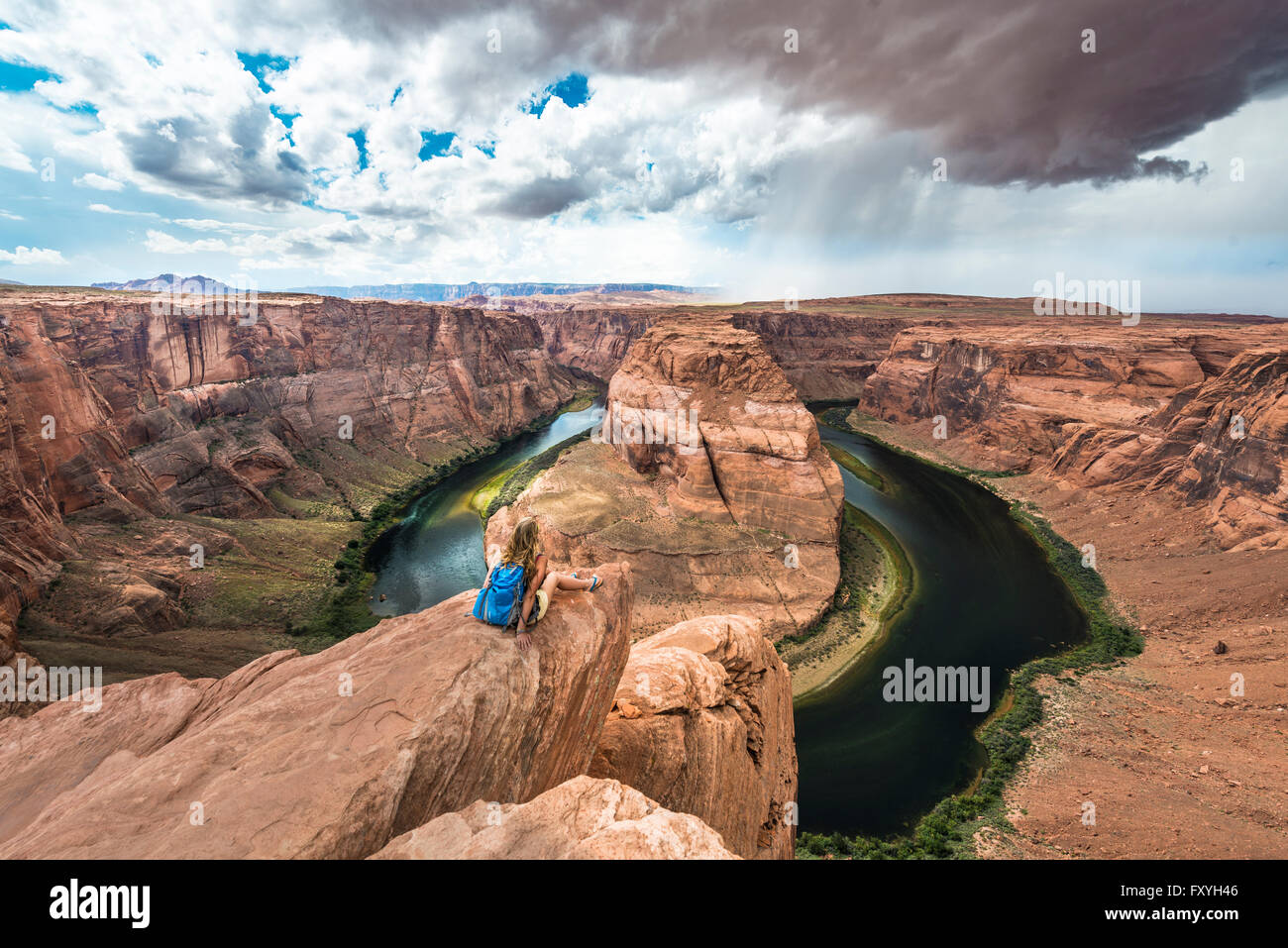 Tourist siting on a rock, looking over the Horseshoe Bend, bend of the Colorado River, King Bend, Glen Canyon National - Stock Image