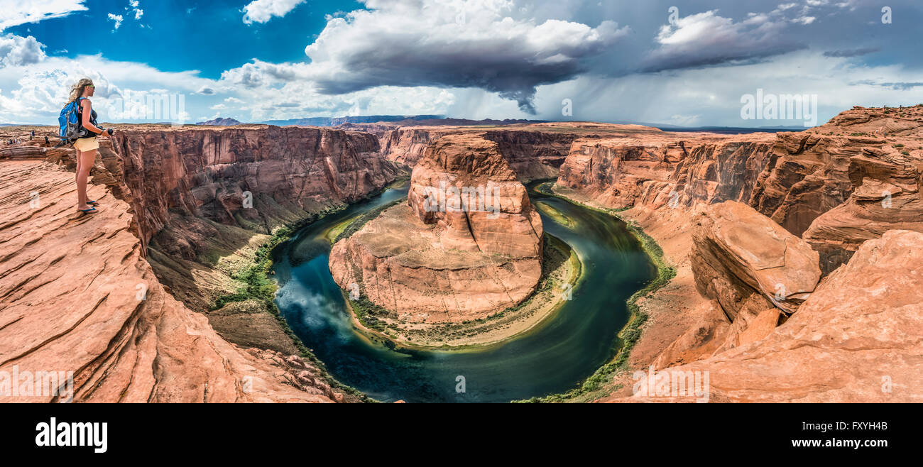 Tourist on a rock overlooking the Horseshoe Bend, bend of the Colorado River, King Bend, Glen Canyon National Recreation Stock Photo