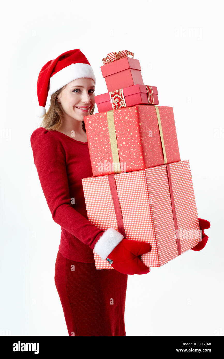 Woman in Santa costume holding Christmas gift boxes with a smile ...