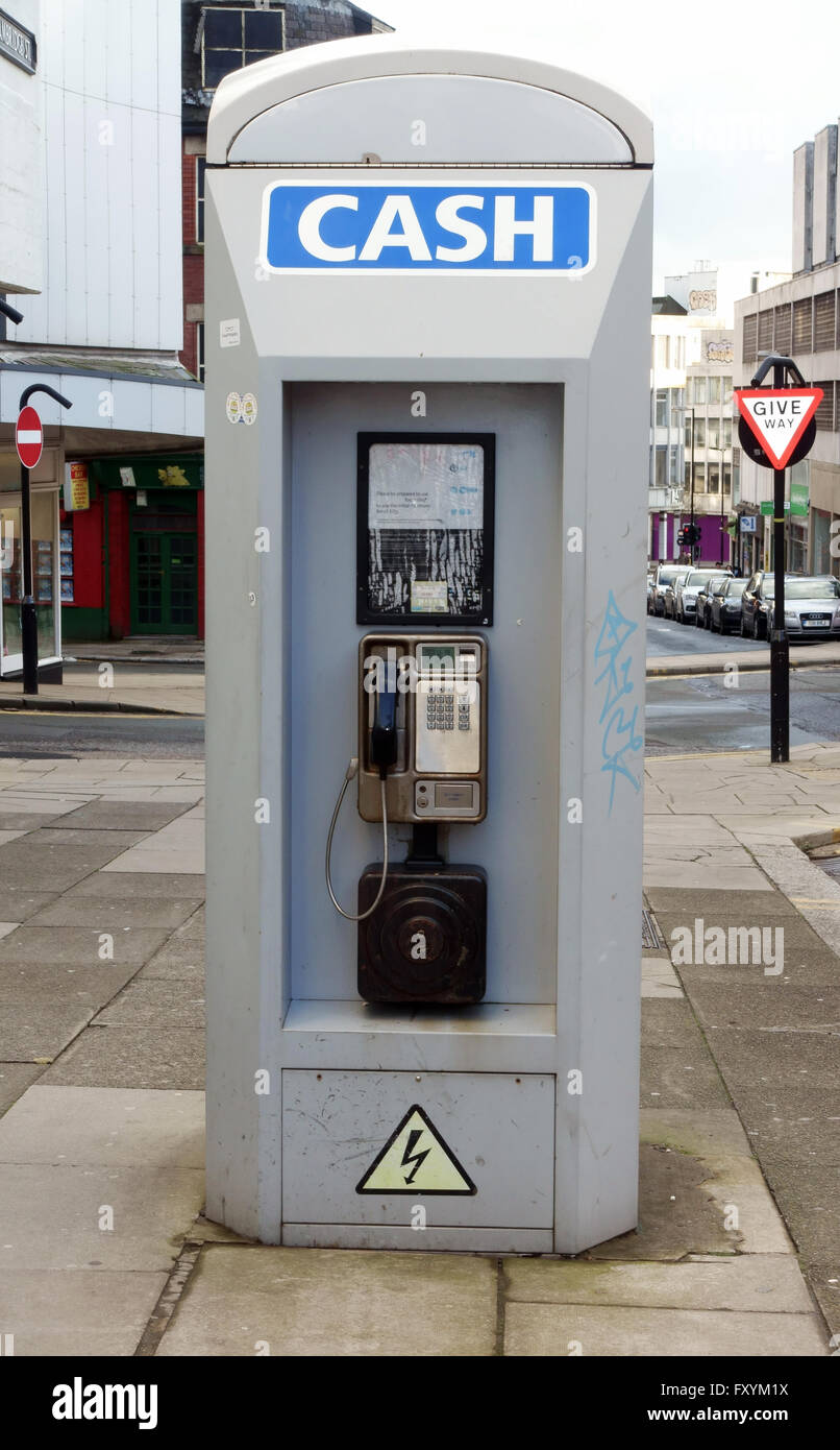A phone box has two use as a public phone and as a cash dispensing machine - Stock Image