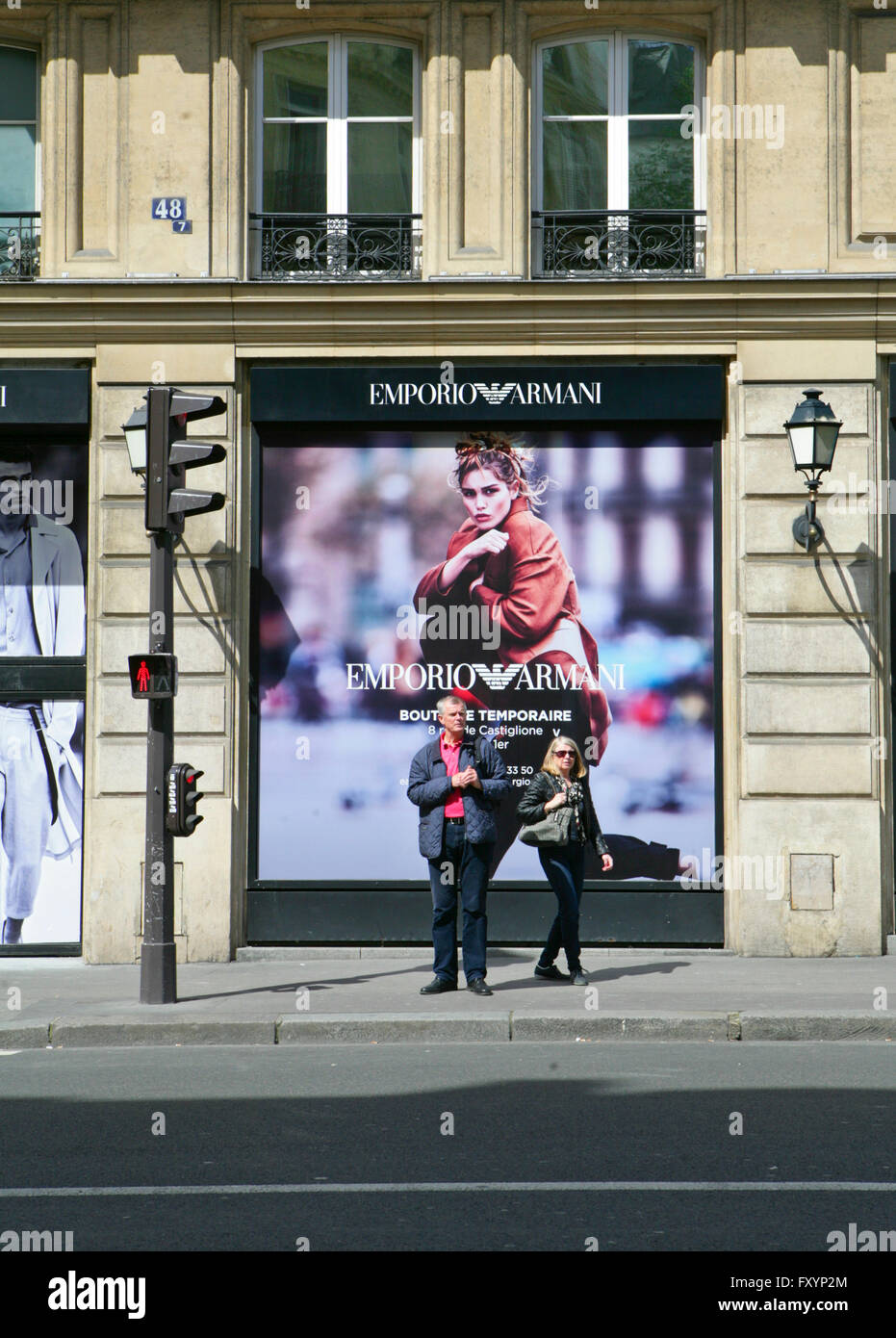 Two people standing in front of the Emporio Armani shop, in Paris,France - Stock Image