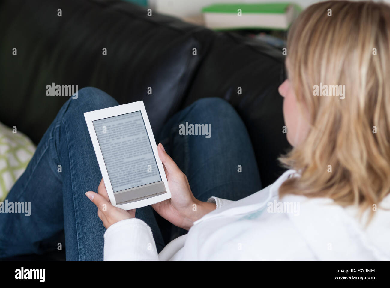 Woman sits on the couch in her free time and reads an ebook. Focus is at the ebook reader. - Stock Image
