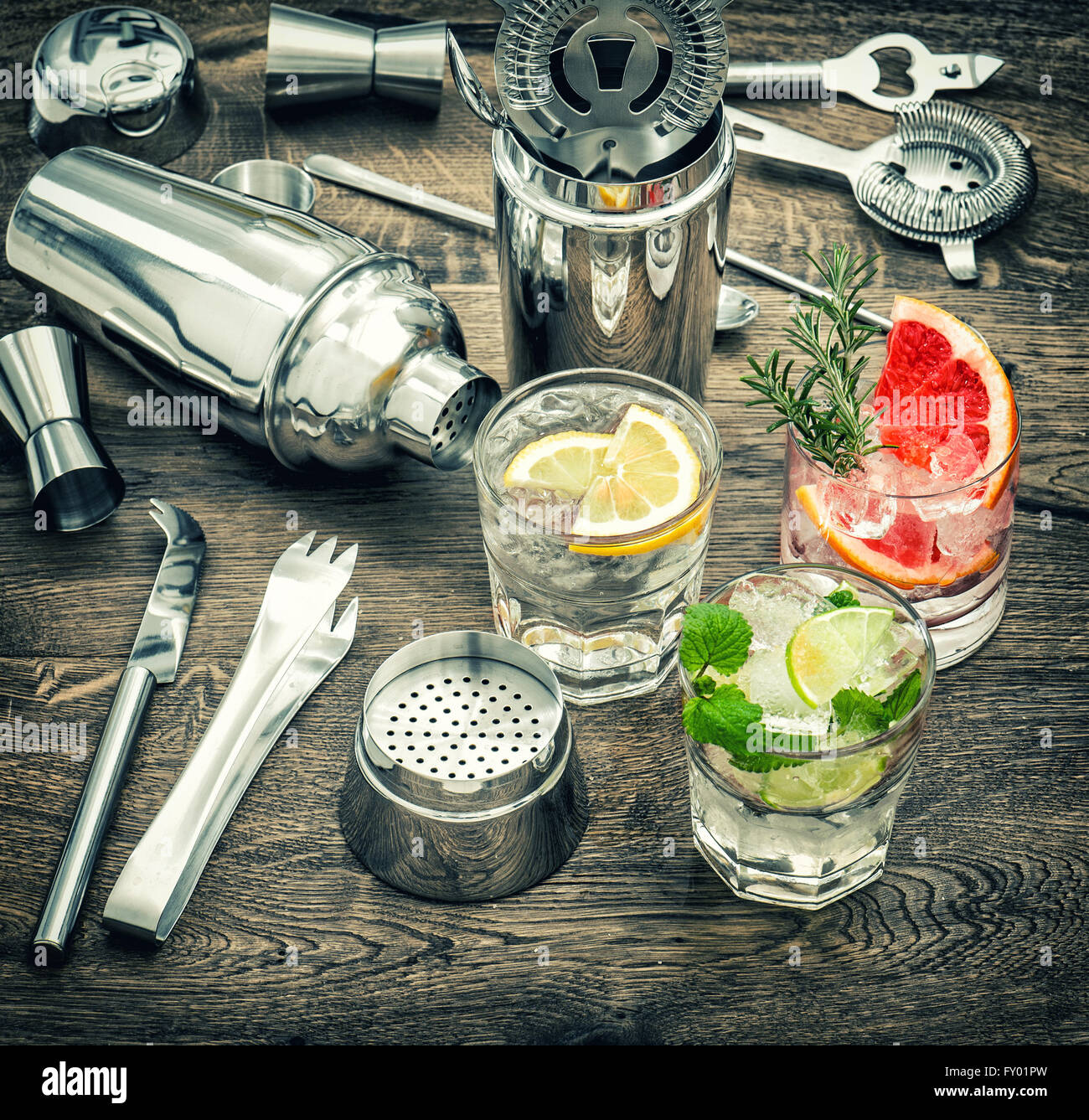 Drinks with ice and tonic water. Cocktail making accessories. Vintage style toned picture - Stock Image