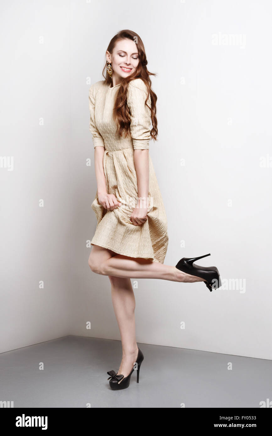 Attractive young woman in golden dress smiles and stands in fashion pose, she weares black high heels. She has long brown hair. Stock Photo