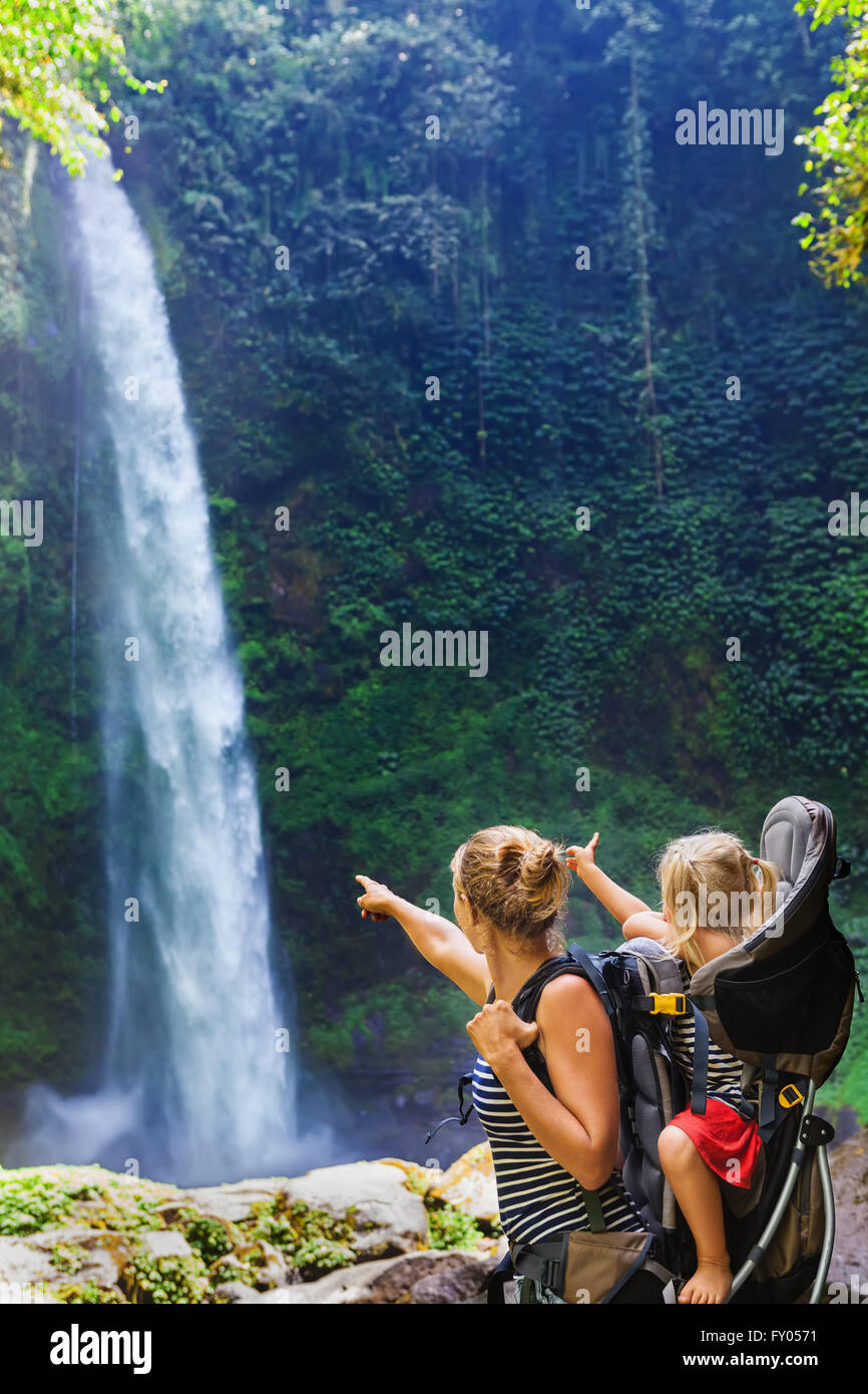 Young happy woman hold little traveller in back baby carrier, explore jungle waterfall in rainforest. - Stock Image