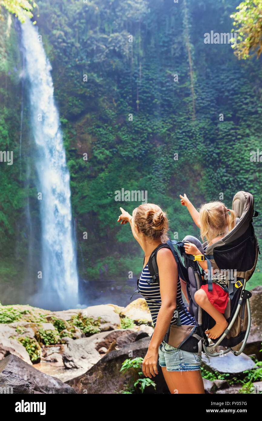 In waterfall pool young happy mother hold little traveller - baby girl in carrying backpack on back. - Stock Image