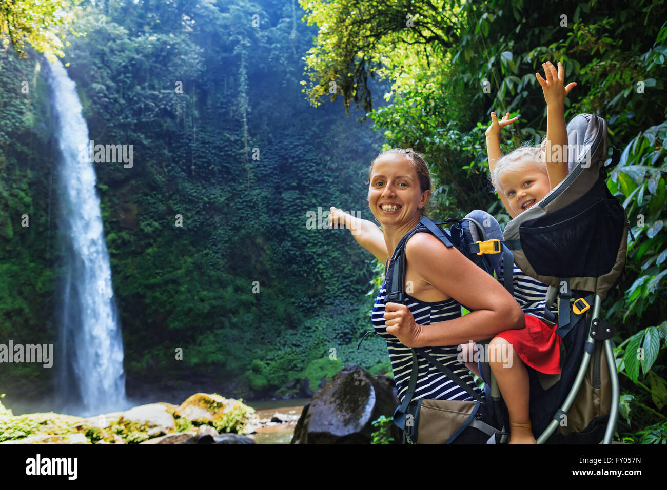 In waterfall pool young happy mother hold little traveller on back - baby girl in carrying backpack enjoying travel - Stock Image