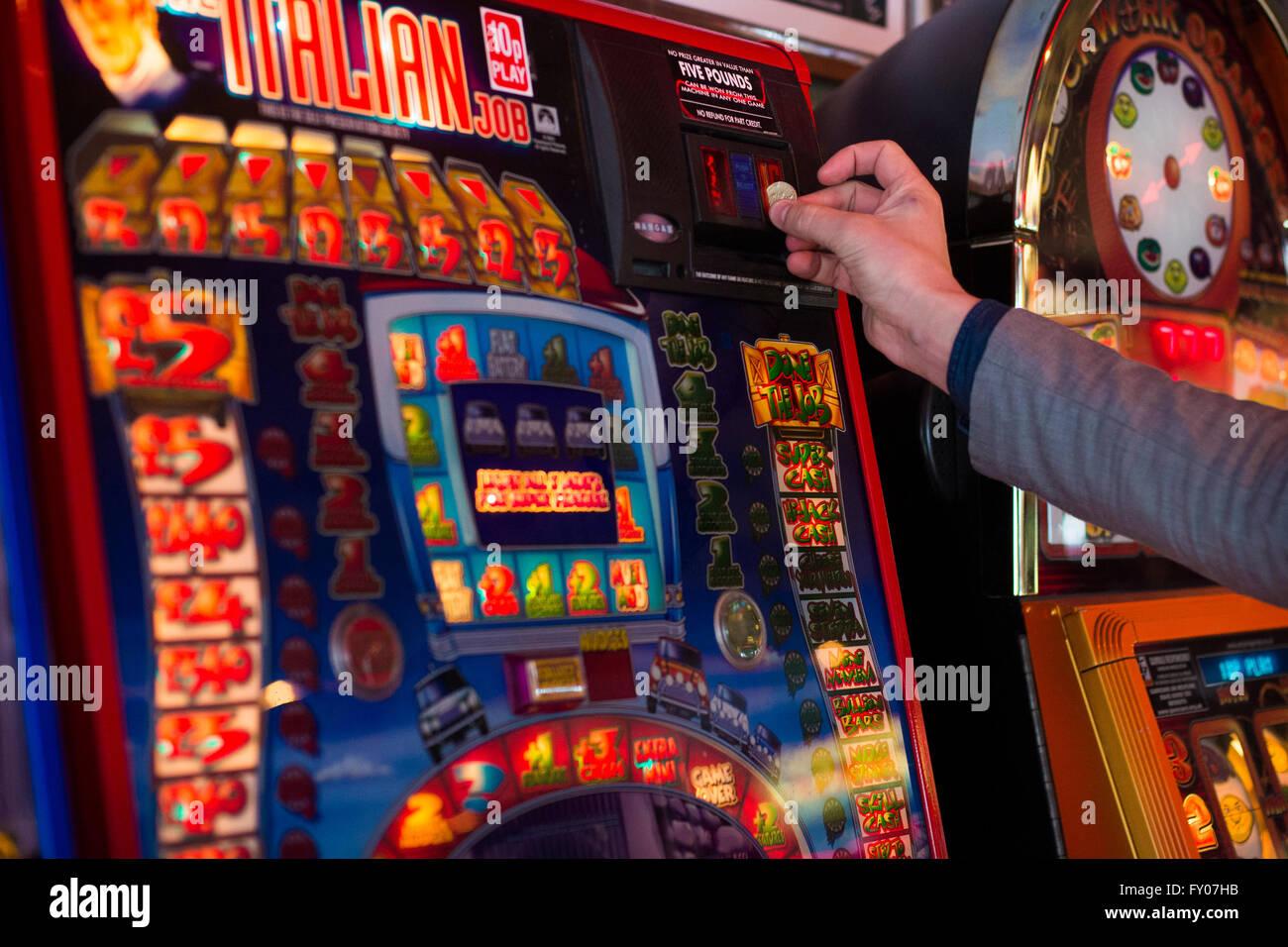 a man's hand putting money into a fruit machine gambling - Stock Image