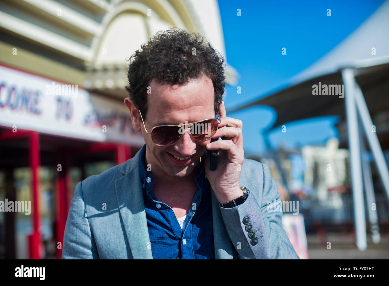 a man talking on his phone and smiling on a sunny day Stock Photo