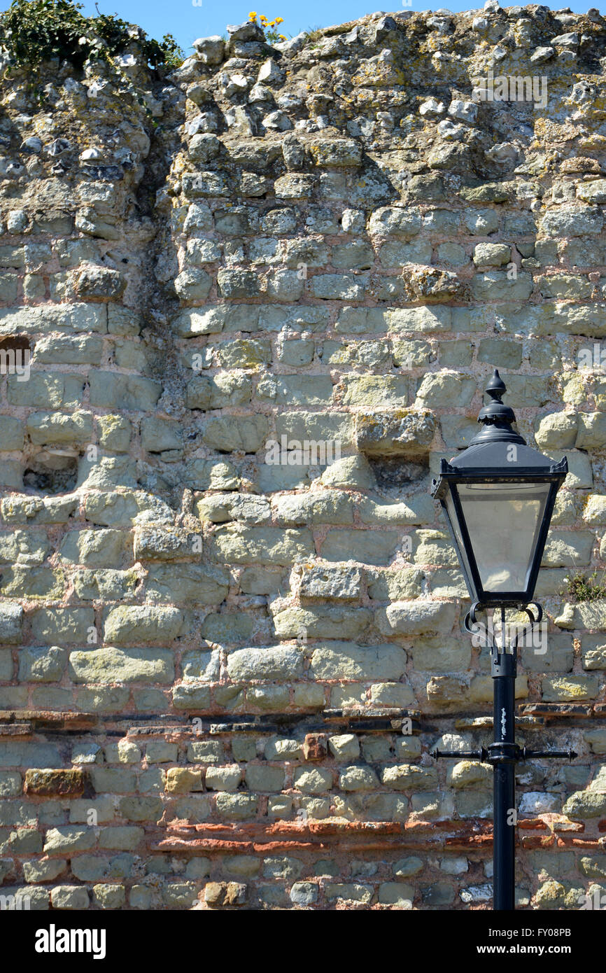 Old street lamp next to ancient wall, Pevensey, UK - Stock Image