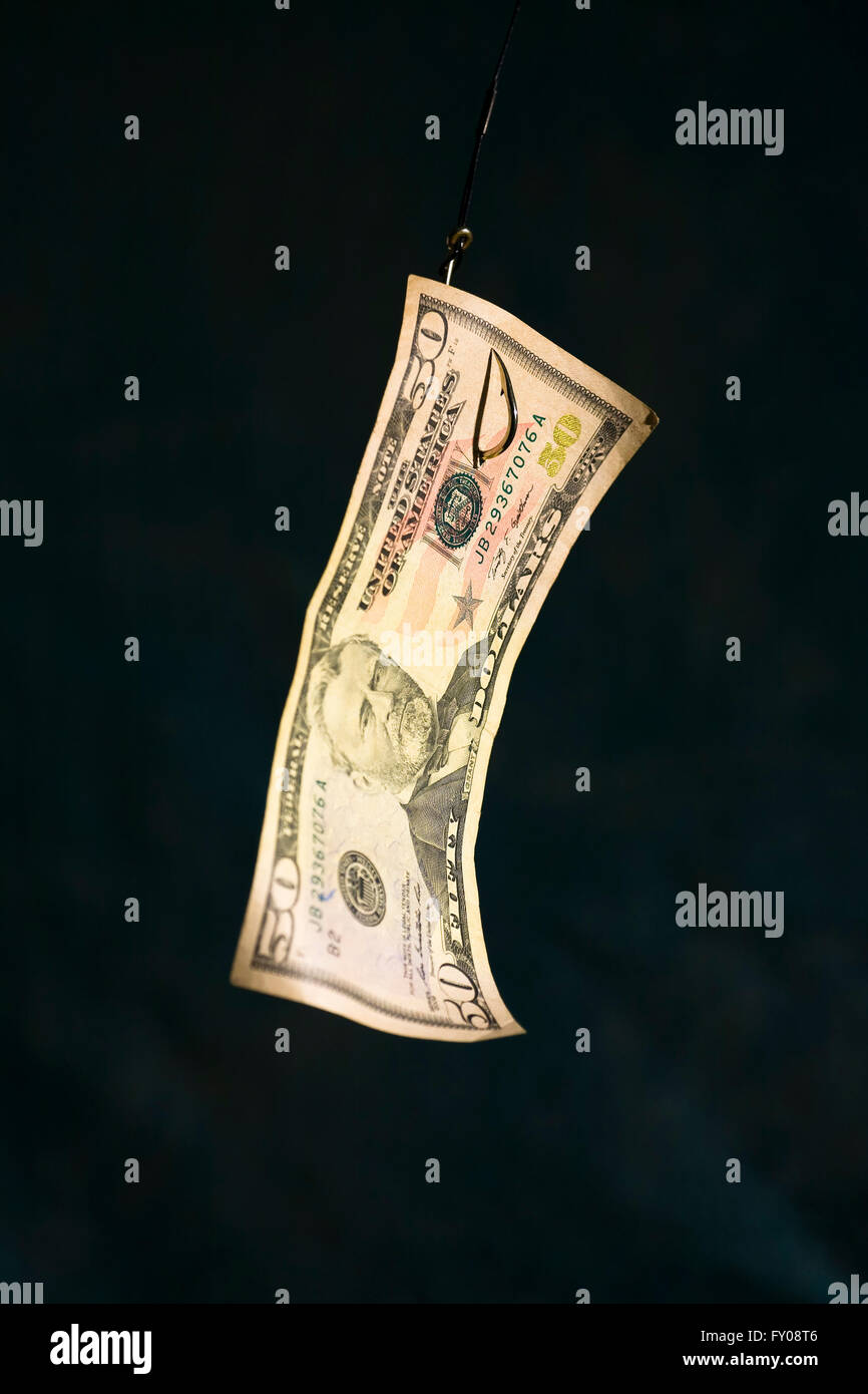 A Fifty Dollar Bill hangs suspended from a fishing hook - Stock Image
