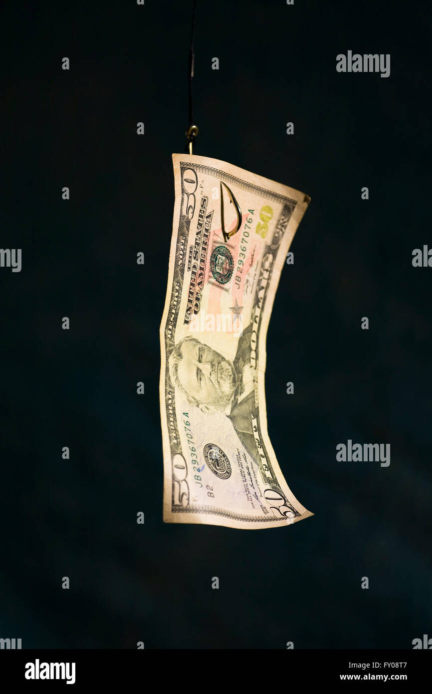 A Fifty Dollar Bill attached to a suspended fishing hook - Stock Image