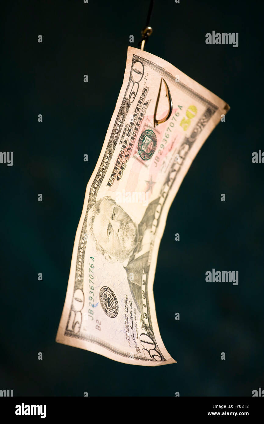 A Fifty Dollar Bill suspended as bait from a gold fish hook - Stock Image