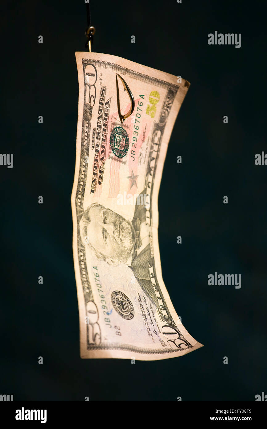 A Fifty Dollar Bill hanging from a fishing hook with dark blue background - Stock Image
