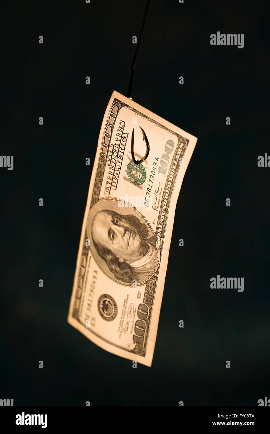 A 100 dollar bill hanging on a fishing hook sharp focus on hook coming through paper on dark blue background - Stock Image