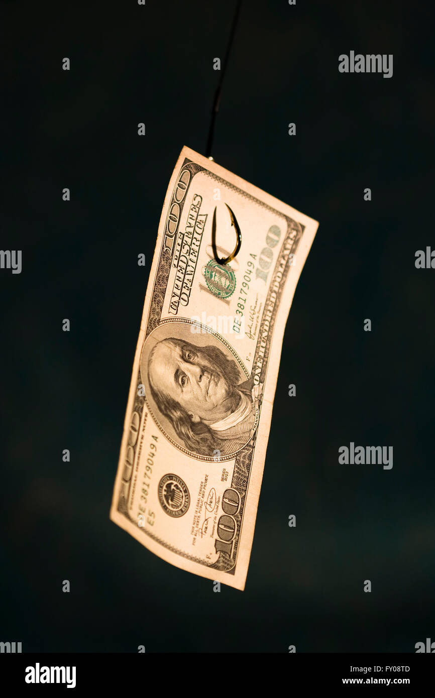 A 100 bill hanging on a fishing hook, focus on Benjamin Franklin's face - Stock Image