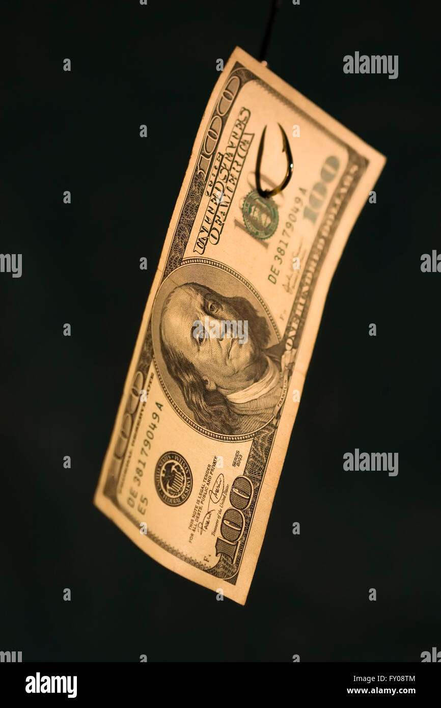 A 100 bill hanging on a fishing hook on a dark blue background with focus on Ben Franklin's face - Stock Image