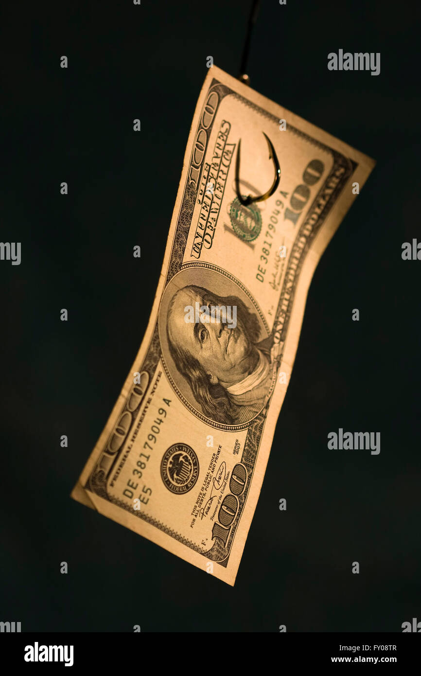 A curved $100 bill hanging on a fishing hook with dark blue background - Stock Image