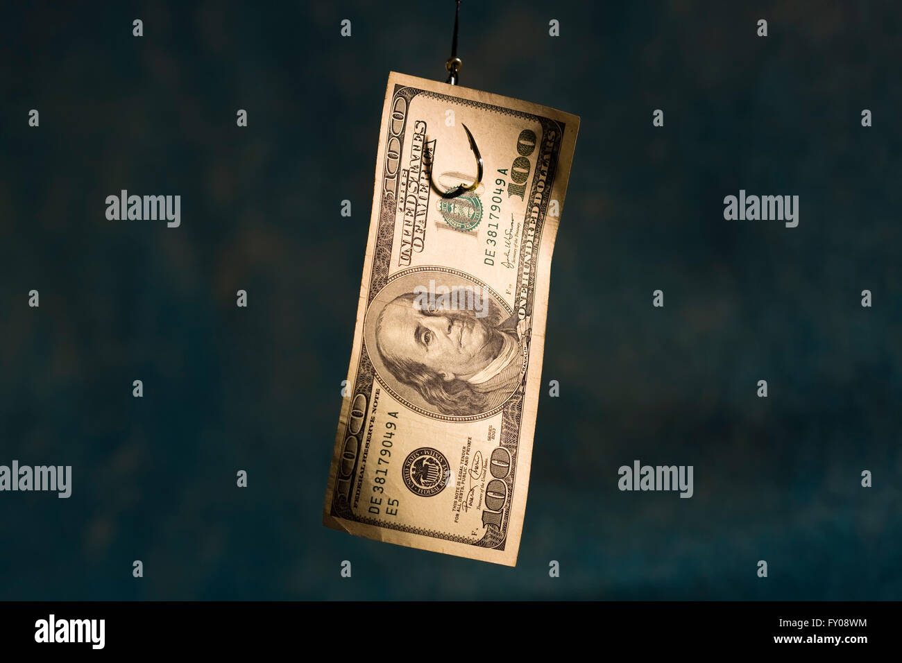 A 100 dollar bill hanging on a fishing hook on a light blue background - Stock Image