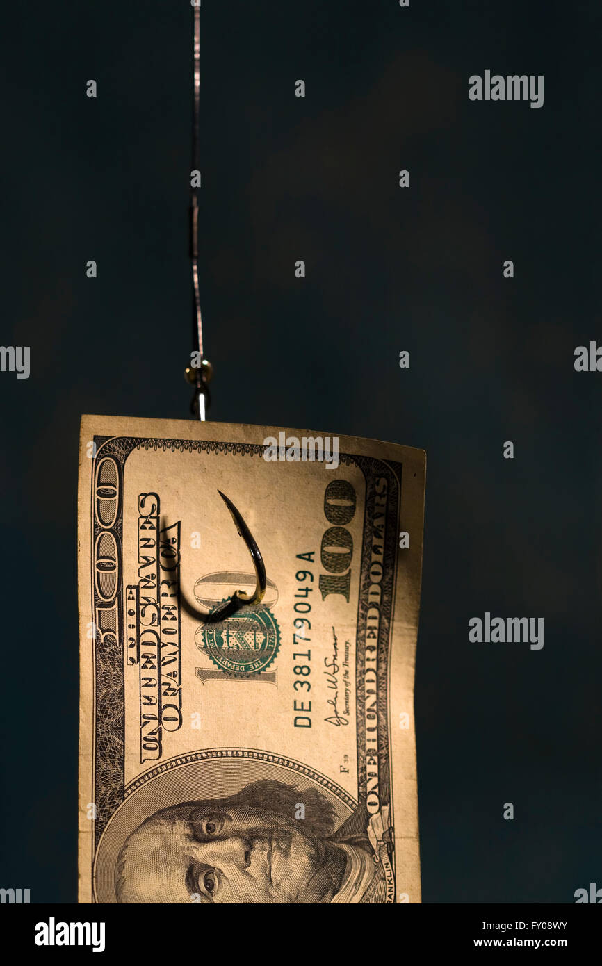 Half of a $100 bill hanging on a fishing hook with light blue background - Stock Image