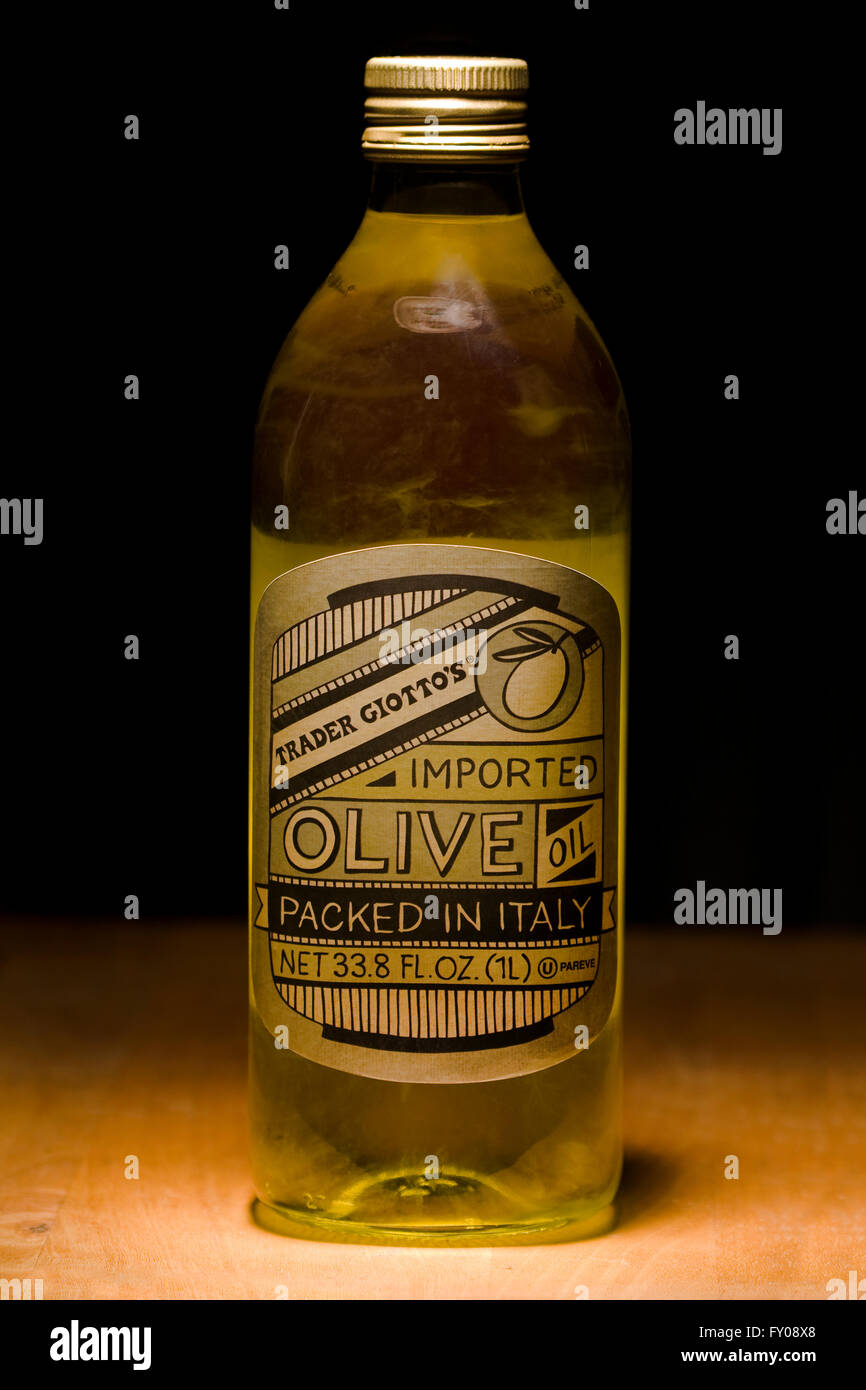 Trader Joe's brand Imported Olive Oil called Trader Giotto's in a 1 Liter glass bottle sitting on a wooden - Stock Image