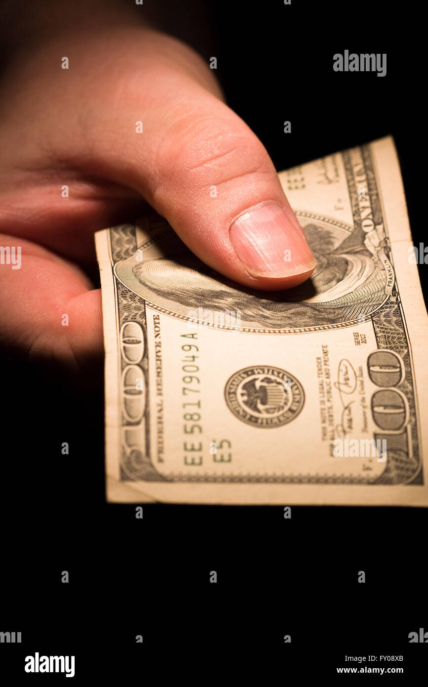 A man's right hand emerging from the shadows holding out a $100 bill - Stock Image
