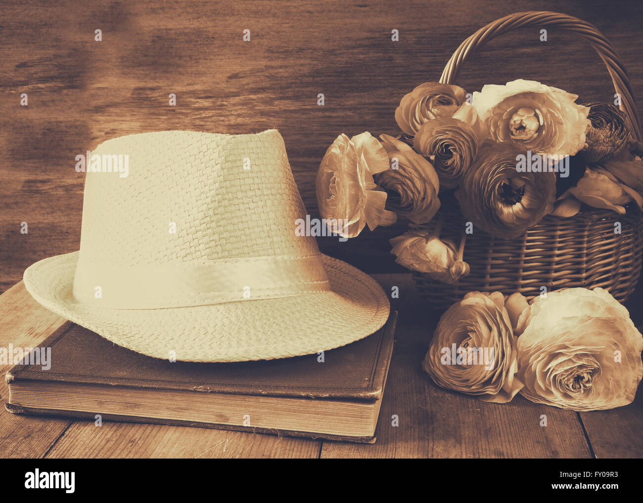 72fbb2ba23a64 fedora hat next to old book and flowers on wooden table. sepia vintage  filtered