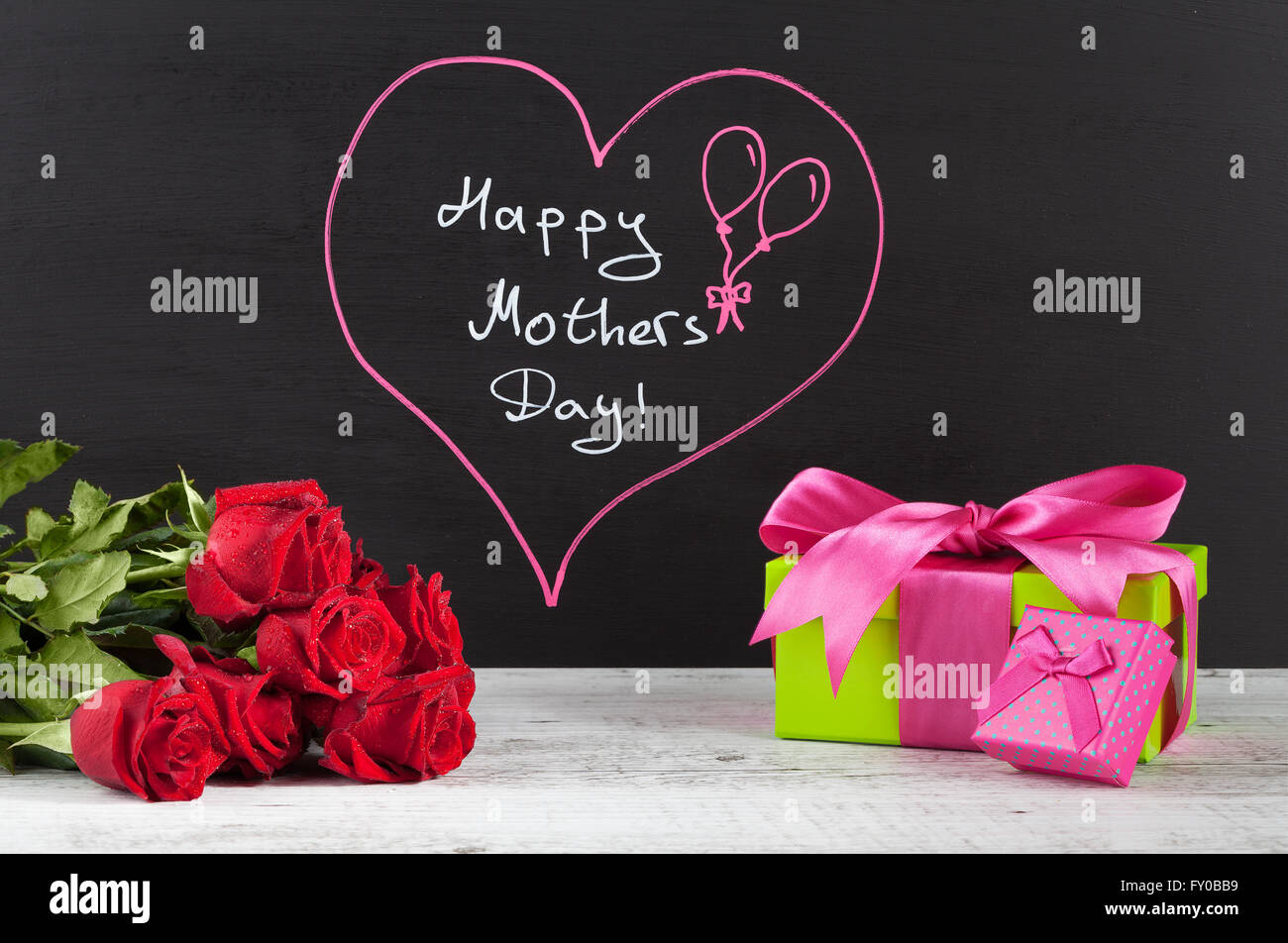 Happy Mother's day composition with red roses and pink gift boxes on white rustic wooden table. Stock Photo