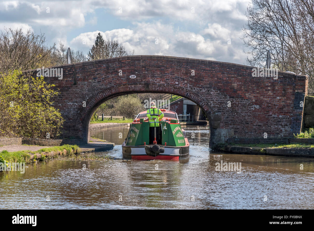 Canal narrowboat passes under an old brick bridge on The National Waterways Museum in Ellesmere Port, Cheshire, - Stock Image