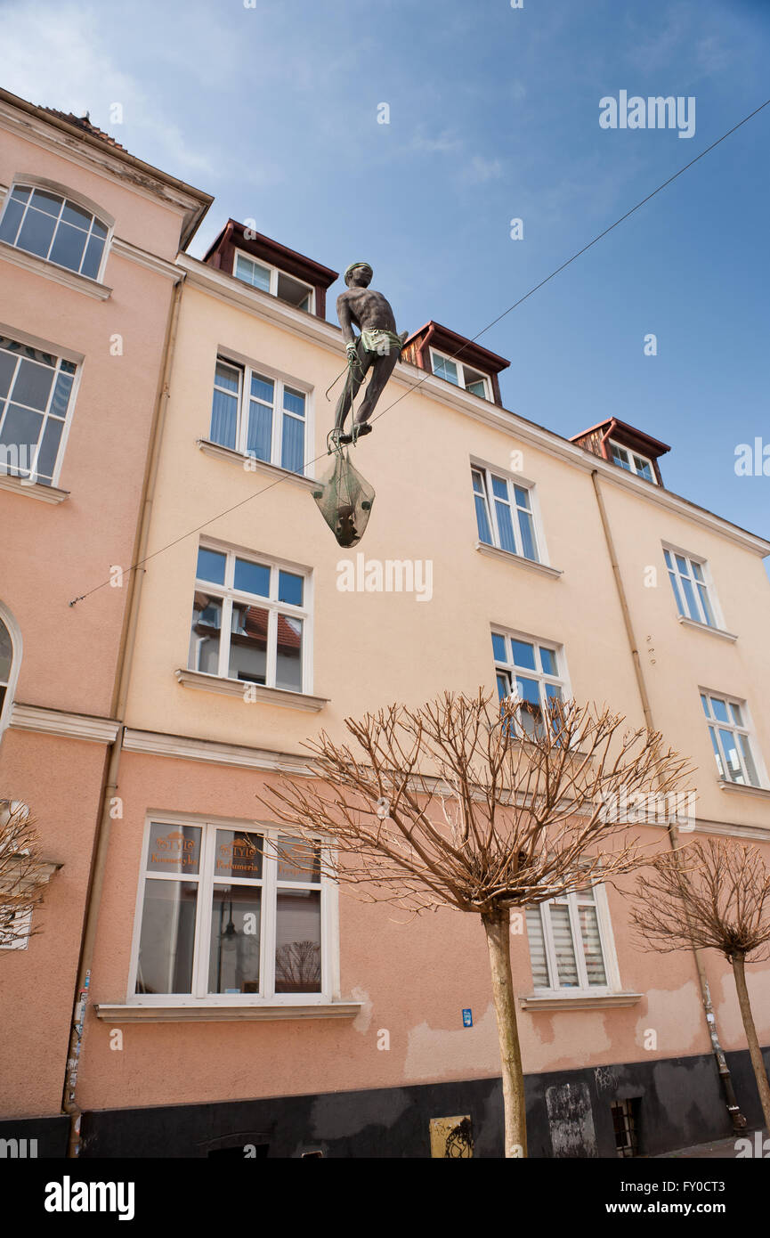 Sculpture of a fisherman balancing walking on the rope between two ...