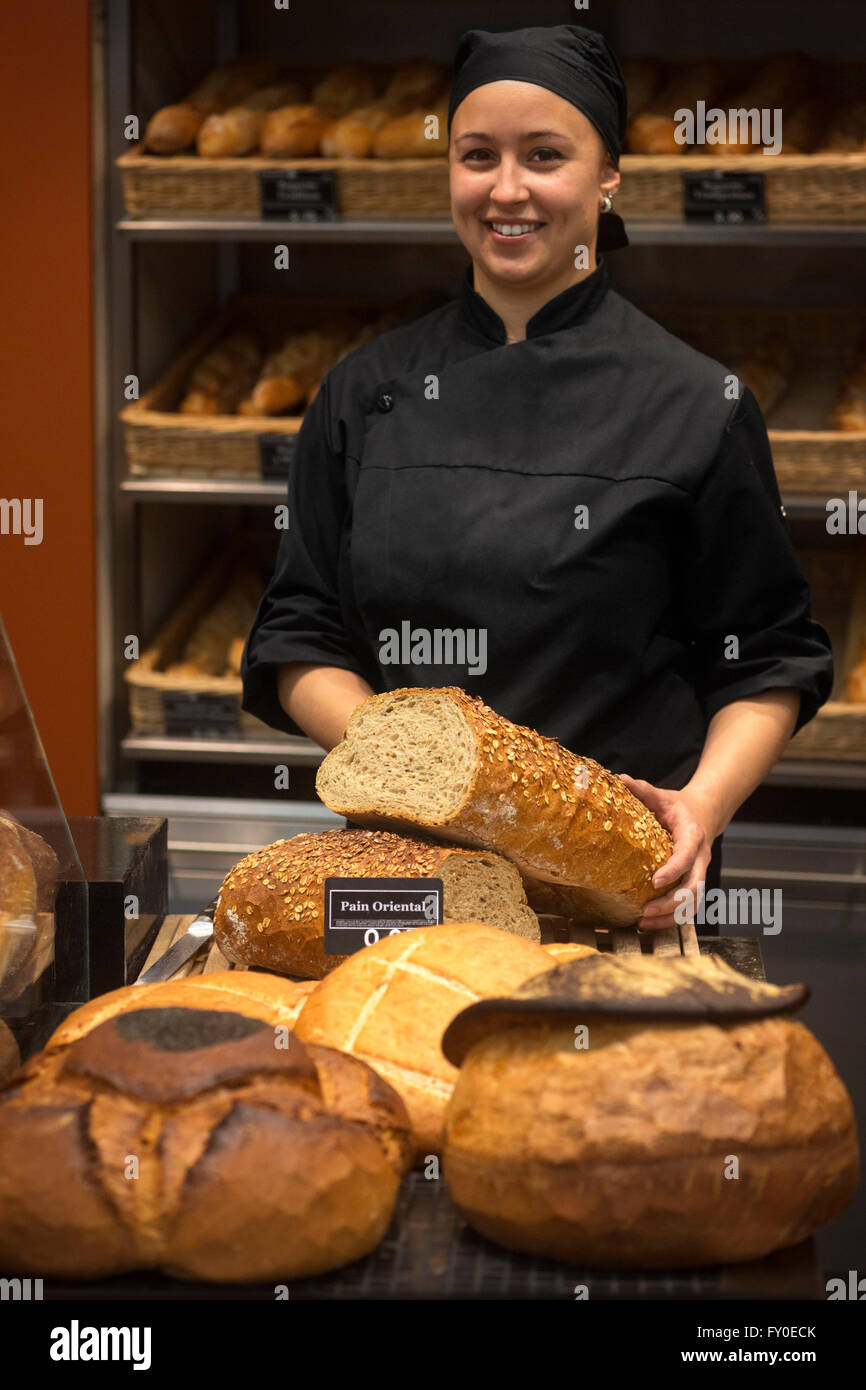 A smiling baker's wife presenting her loafs of bread. Bakery saleswoman in black uniform holding loaf of bread. - Stock Image