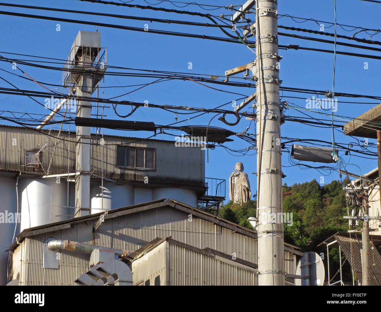 Buddah on hilltop through industrial powerlines Matsuyama Japan - Stock Image