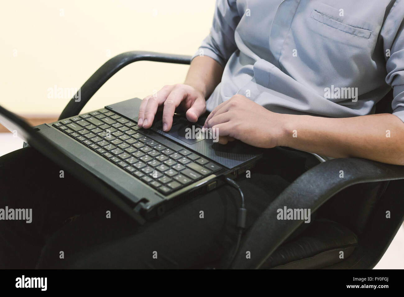 Adult man sit and typing laptop on your leg in home office . Stock Photo