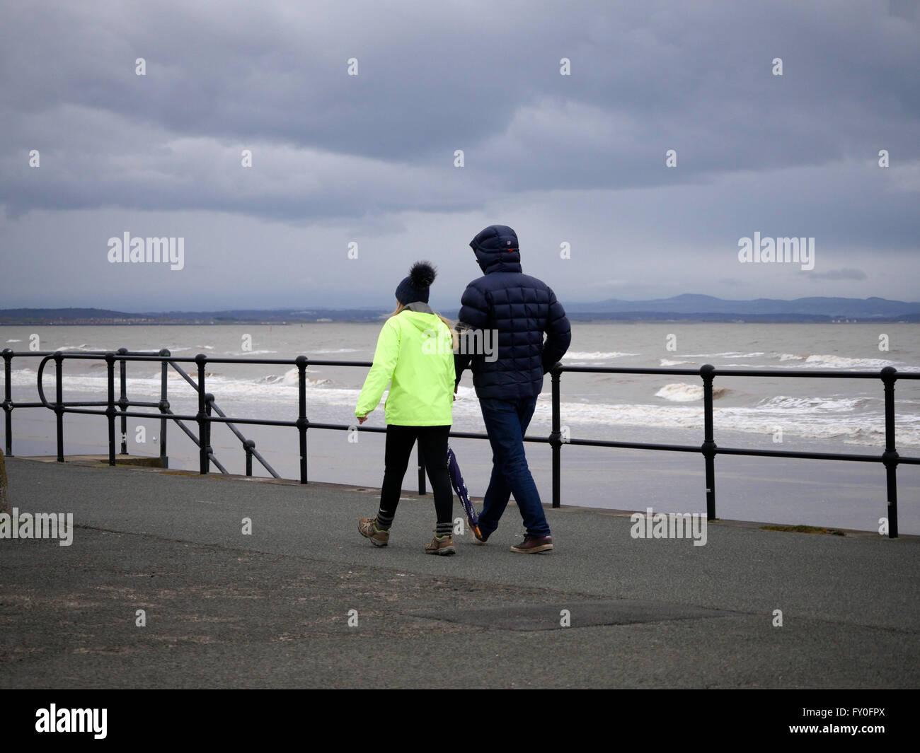 People enjoying a walk on Crosby Promenade in Winter - Stock Image