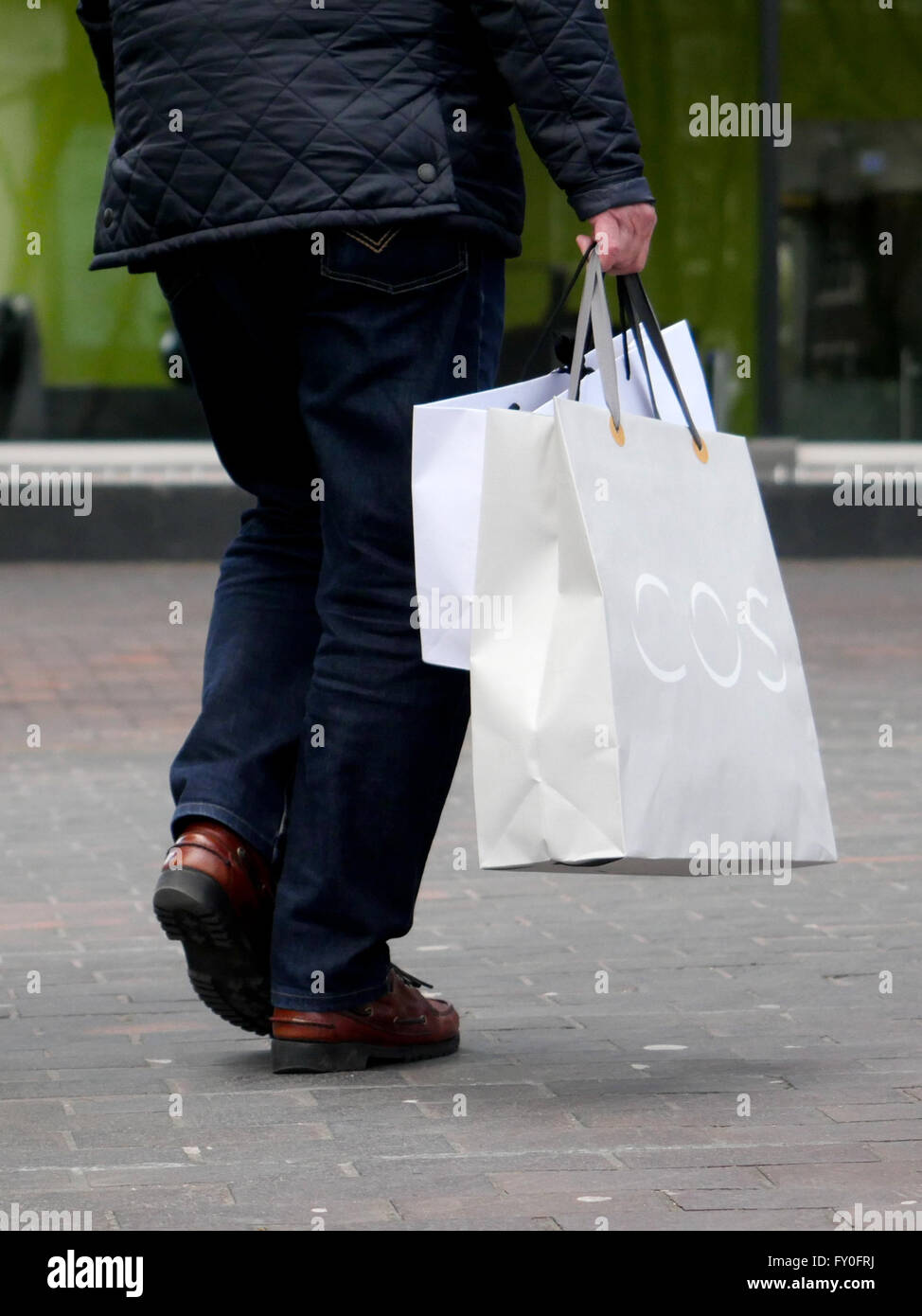 Man holding shopping bags in the street, close-up of legs - Stock Image