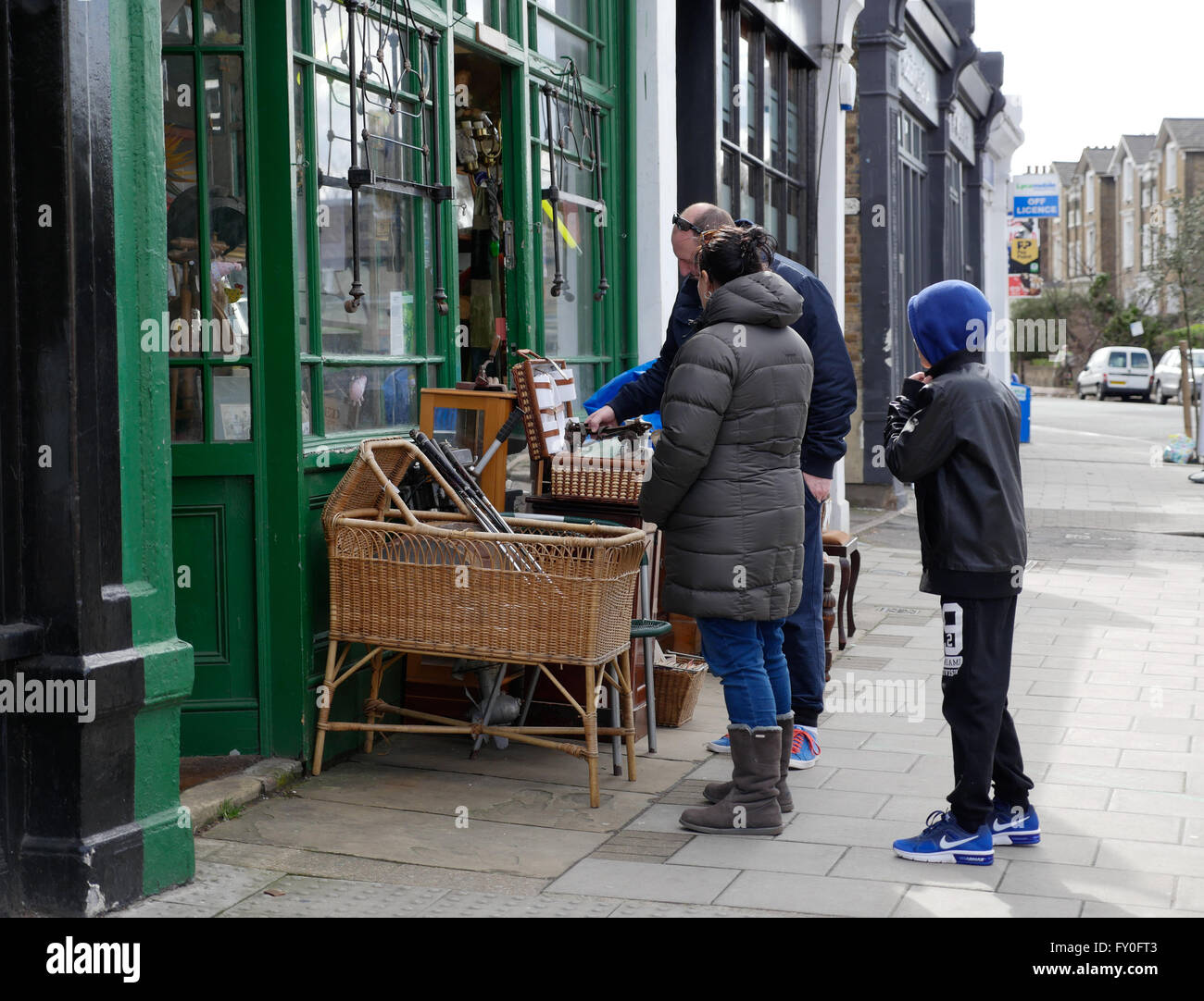 A family browse in the window of a curiosity shop in London - Stock Image