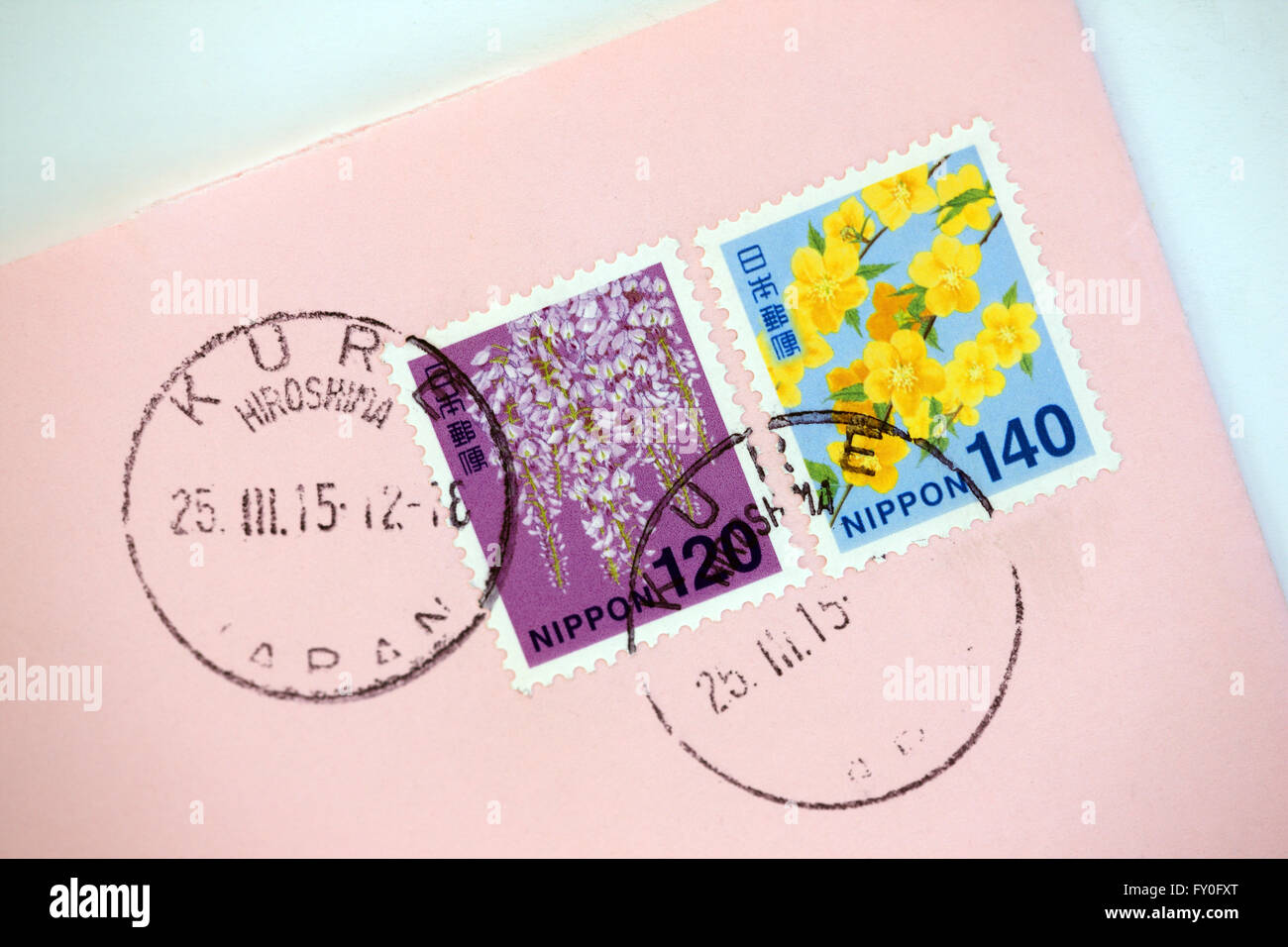 Japanese stamps on a pink envelope and Hiroshima postmark - Stock Image