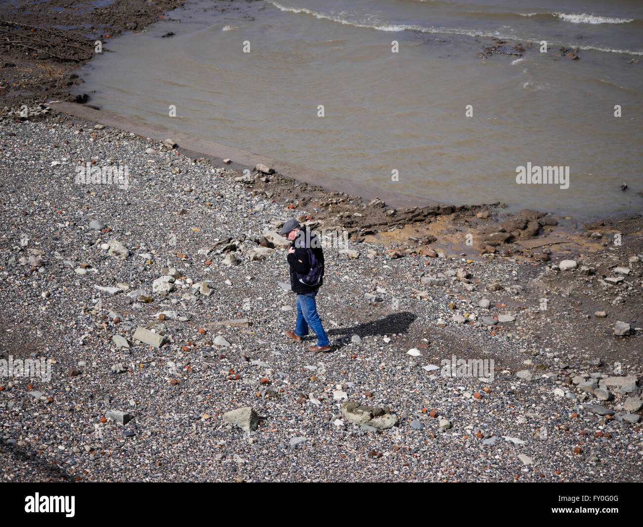 A man searches the Foreshore near Greenwich Pier - Stock Image