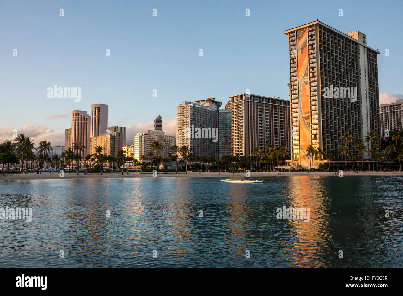 A view of the Hilton Hawaiian Village Waikiki Beach Resort and surrounding hotels at sunset. - Stock Image