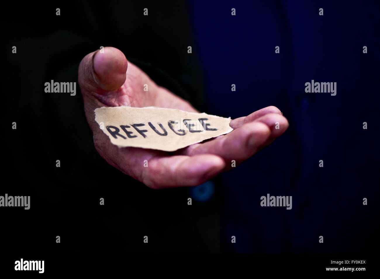 closeup of the hand of an old man with a piece of paper with the word refugee, with a dramatic effect - Stock Image