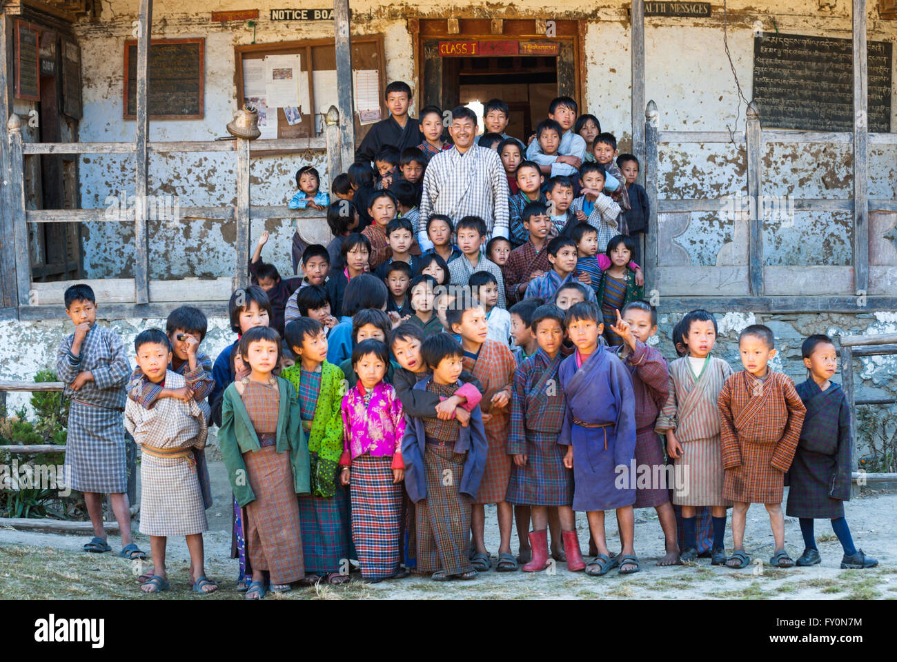 Children and principal wearing traditional dress standing on steps of dilapidated primary school in Nimshong vilage, - Stock Image