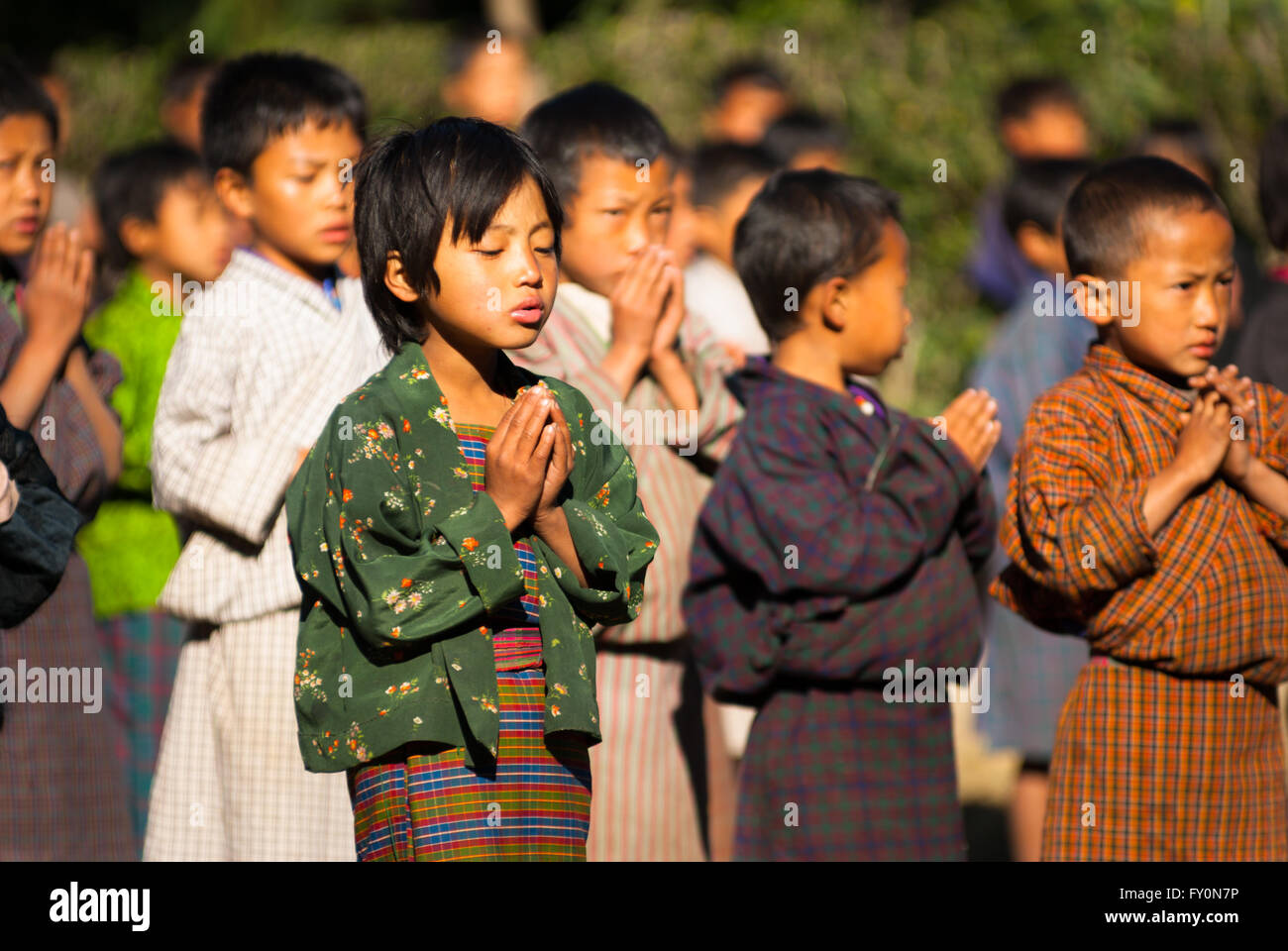 Students wearing traditional dress say prayers at morning assembly at a primary school in Nimshong village in southern - Stock Image