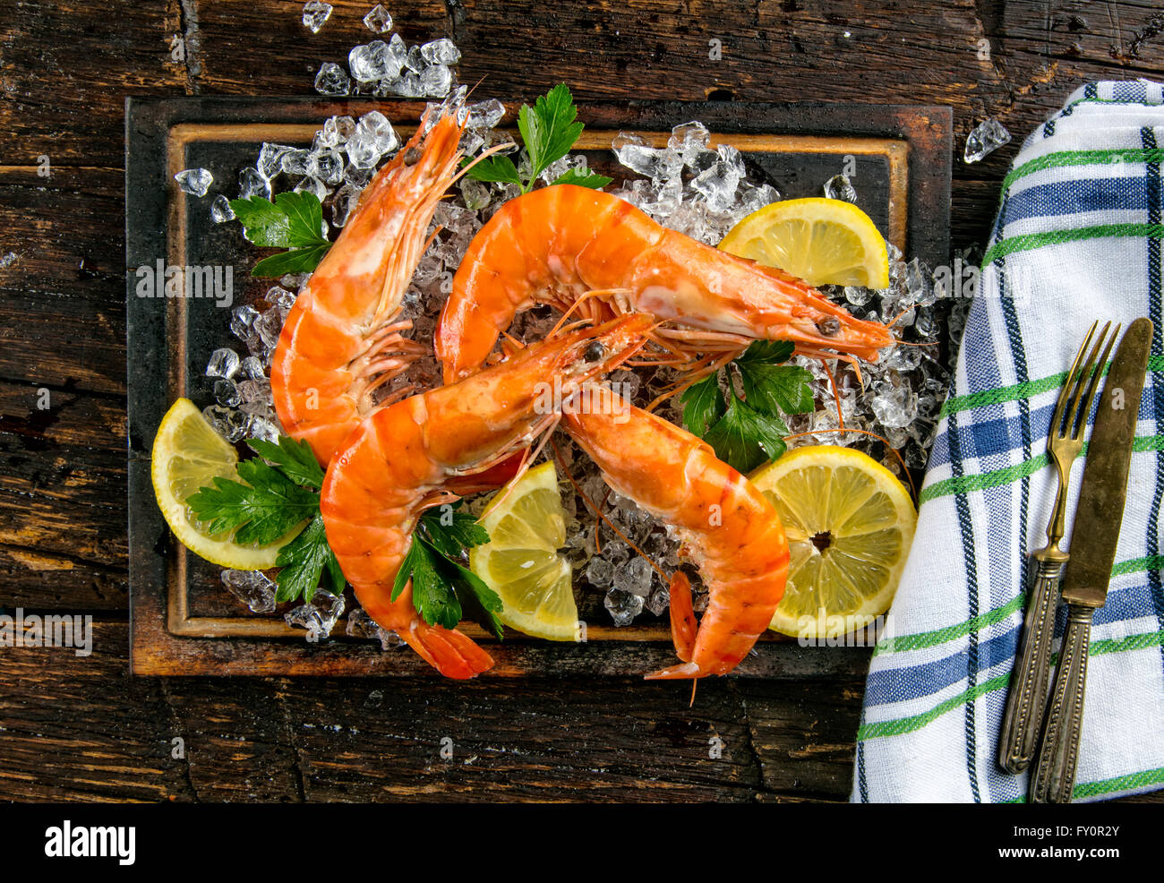 Cooked prawns served on dark wood - Stock Image