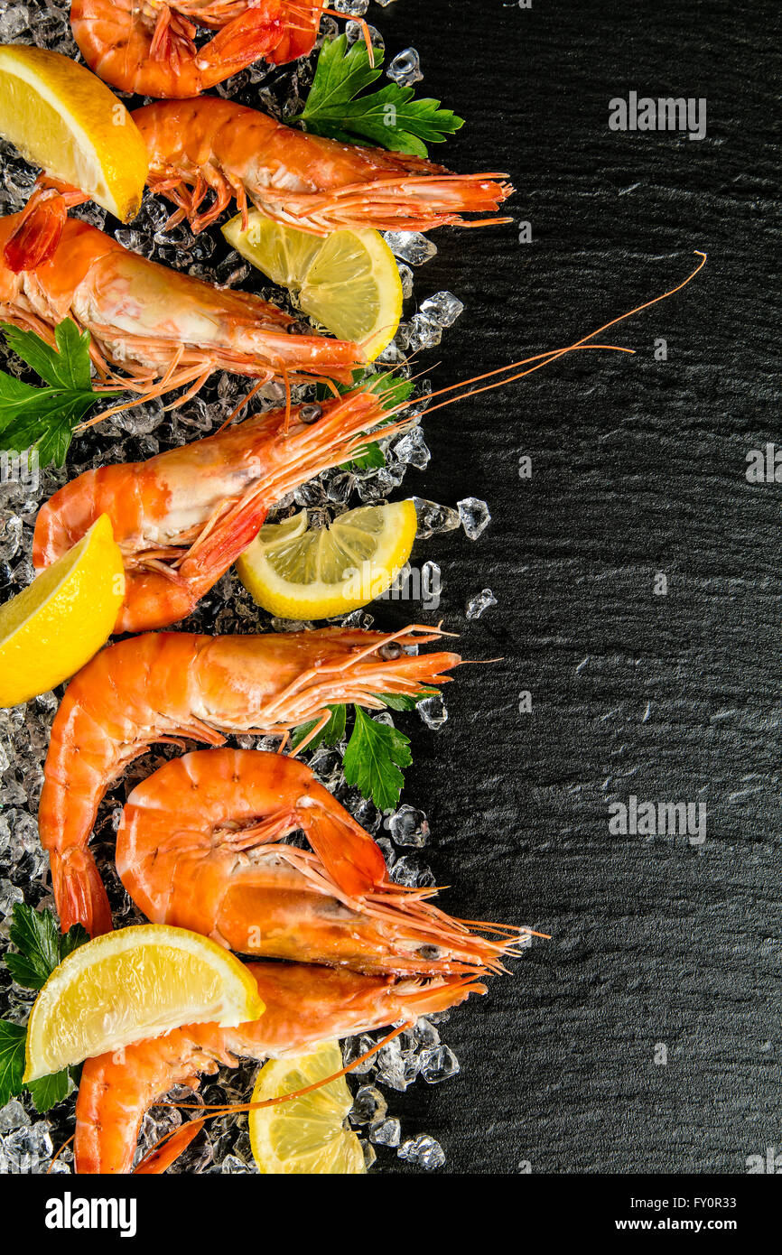 Cooked prawns served on black stone - Stock Image