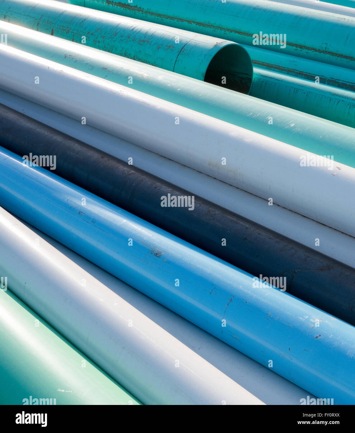 Abstract of blue, white and green water pipes stacked at a construction site on a sunny day Stock Photo