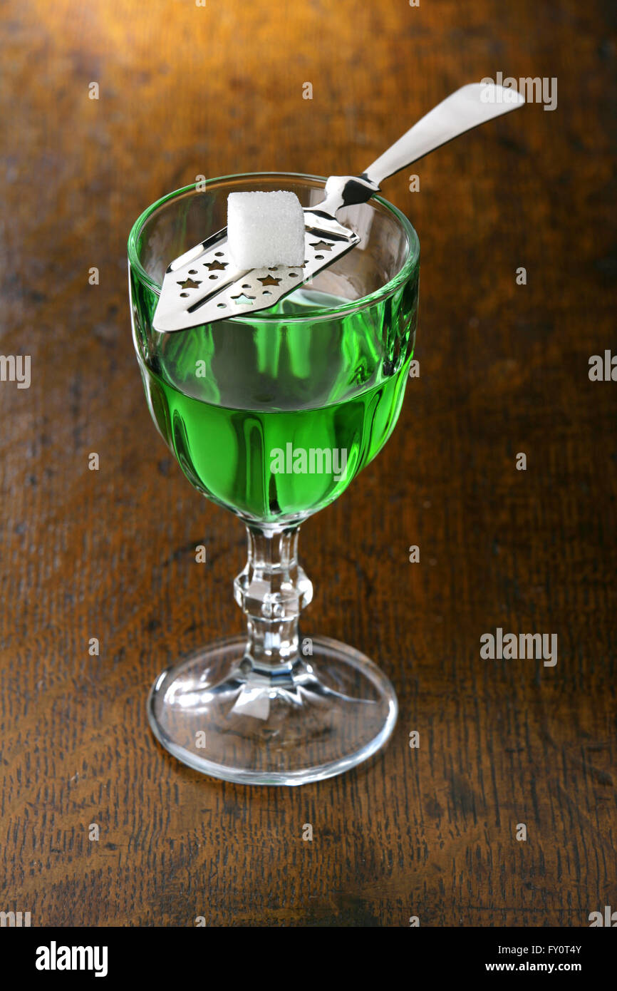 Glass of Absinthe with Absinthe Spoon and sugar on a bar top. - Stock Image