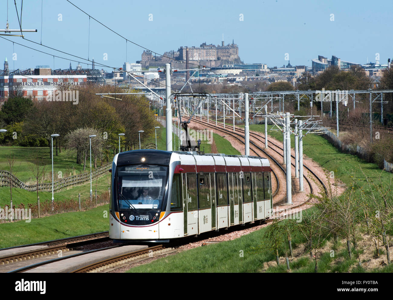 Edinburgh tram on route from the city centre to the airport with Edinburgh castle in the distance. Stock Photo