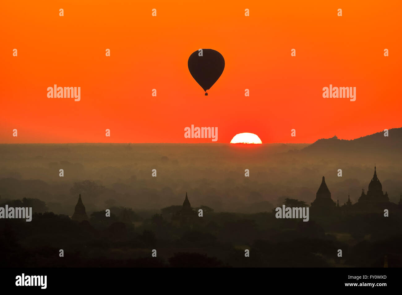 Sun rising over the horizon and hot air balloon flying at Old Bagan with orange sky and temple silhouettes, Myanmar Stock Photo