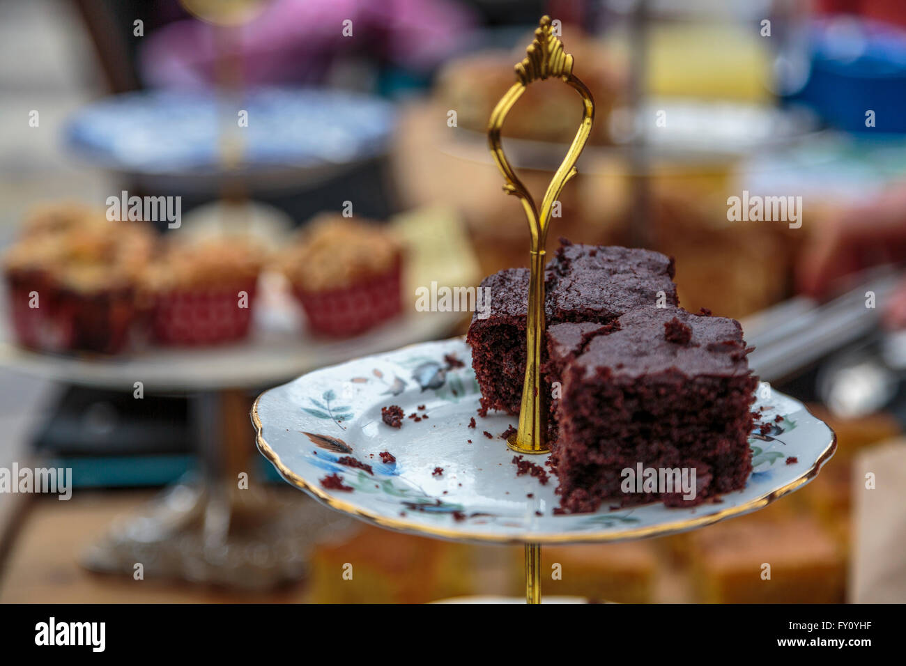 A home made piece of chocolate brownie cake on an ornate china serving dish wth gold handle - Stock Image